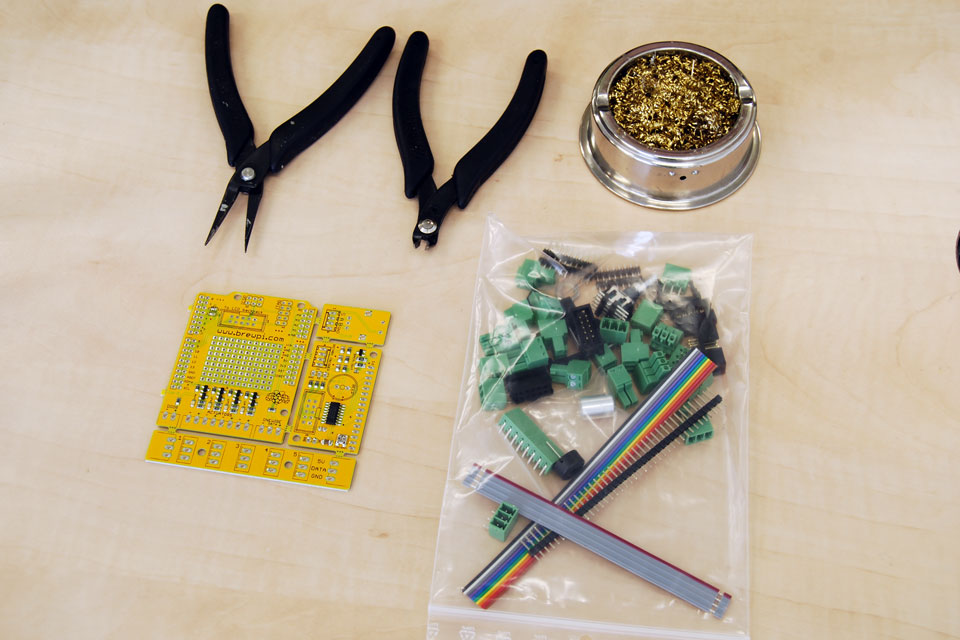 This is what you bought from the shop: a 4-part PCB with SMT components soldered and a bag of through hole parts. Go ahead and empty the bag on your desk. Also in the picture: golden curl tip cleaner (highly recommended!) and the needed side cutter and pliers.